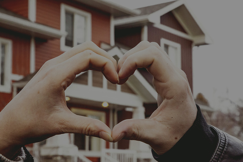 hands in heart shape in front of townhouse